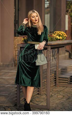 Glamorous Clutch Accessory. Fashion Blog. Elegant Woman In Green Velour Dress. Velvet Fashion Trend.