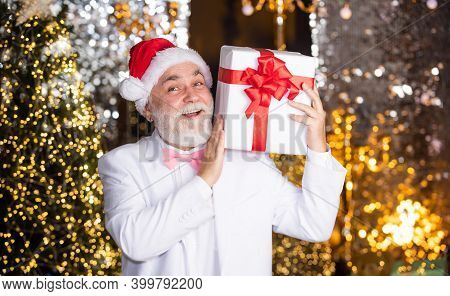 Christmas Preparation. Senior Man Santa Hat Hold Gift Box. Bearded Businessman Present. Holiday Deco