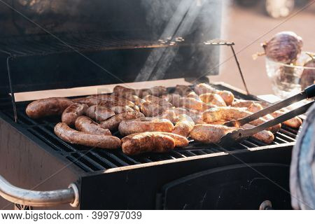 Grilled Sausages Or Bratwurst On Grill With Smoke And Flame. Delicious German Sausages On Barbecue G