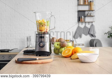Modern Blender With Fresh Fruits And Cutting Board On Table In Kitchen