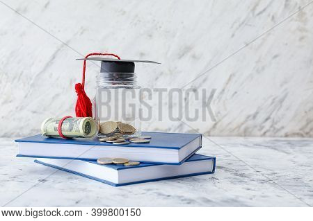 Graduation Hat, Books And Jar With Money On Table. Tuition Fees Concept