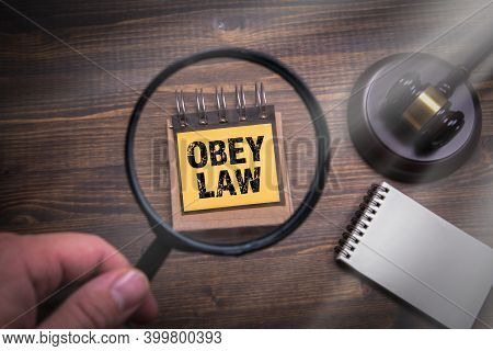 Obey Law Concept. Hand With Magnifying Glass