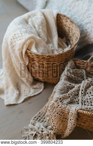 High Angle View Of Wicker Basket With Plaid And Textile Standing On Wooden Floor. Vertical Photo Of