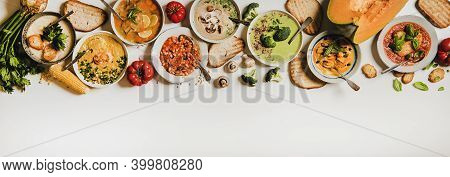 Flat-lay Of Creamy Homemade Soup In Plates With Bread Slices Over White Plain Table Background, Top