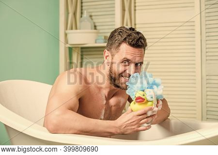 Sexy Man In Bathroom. Sex And Relaxation Concept. Man Wash Muscular Body With Foam Sponge. Wash Off