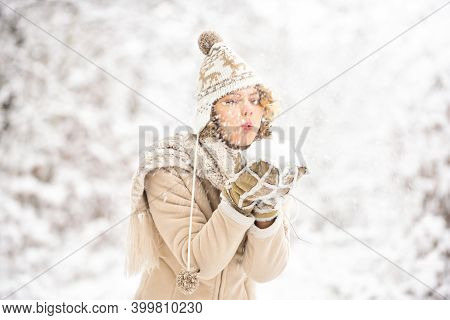 Happy Woman Blow Snow From Hands. Girl In Trendy Winter Coat. Girl Wear Warm Mittens And Hat. Good M