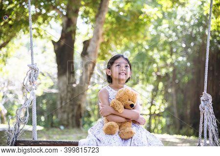 Happy Child Hug Teddy Bear In Green Park Playground. Teddy Bear Best Friend For Little Kids Cute Gir