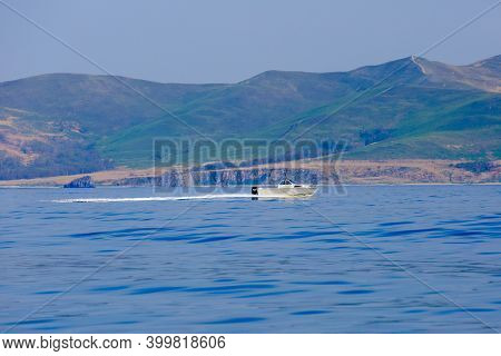 The White Boat Sails On A Calm Blue Porch Against The Backdrop Of The Islands. Motor Boat Trips