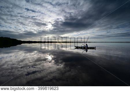 Everglades National Park, Florida - December 12, 2020 - Active Senior Kayaks At Sunset Under Dramati