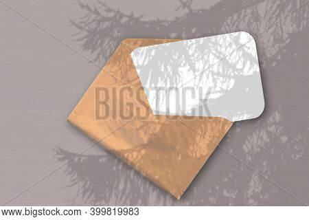 An Envelope With Sheet Of Textured White Paper On The Brawn Background Of The Table. Mockup Overlay