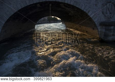 A Pleasure Boat Sails Under A Bridge Over The Seine In Paris