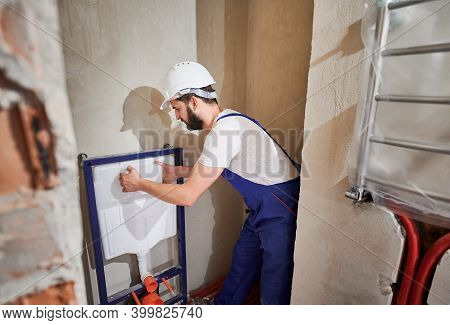 Male Plumber In Work Overalls Installing Concealed Toilet Frame In Bathroom. Bearded Man In Safety H