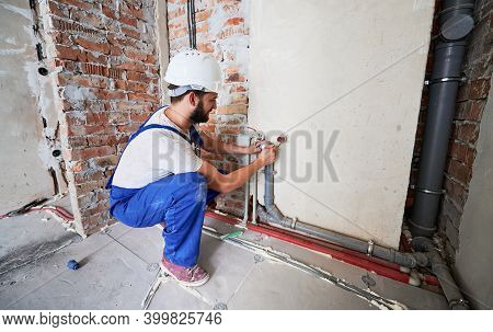 Bearded Young Man In Work Overalls Installing Heating Pipes In Apartment. Male Worker In Safety Helm