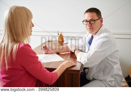 Woman Discussing Plastic Surgery With Doctor In Modern Clinic. Male Surgeon Looking To The Camera, S