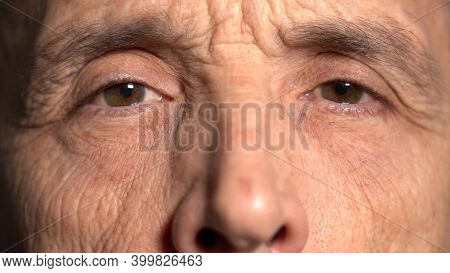 Close-up. The Elderly Man Stared At The Camera. Reflection Of Light In The Eyes. Old Age Concept.