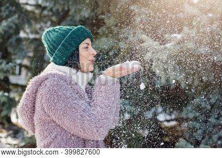 Portrait Of Young Cozy Woman In Warm Clothes In Sunny Winter Day. Snow Blowing Winter Fun. Beauty Wi