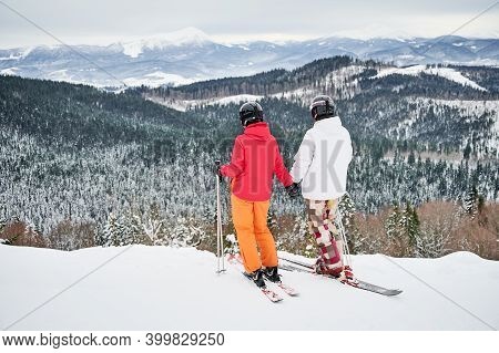 Back View Of Couple Skiers Wearing Ski Suits And Ski Equipment In Winter Mountains, Enjoying Snowy W