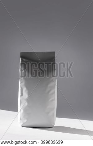 Blank Foil Food Or Drink Bag On White Background In Minimal Style, Natural Light Shadow. Monochrome