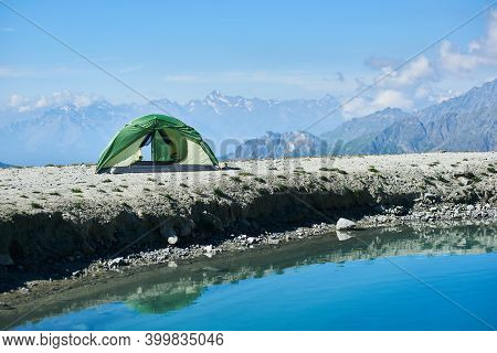 Panoramic View Of Blue Lake And Tourist Tent In Mountain Valley. Picturesque Scenery Of Camp Tent Ne