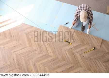 Worker Installing Laminated Wooden Floor Indoors, Above View