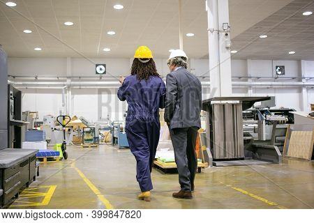 Rear View Of Boss Standing At Factory And Listening Plant Worker. African American Factory Employee