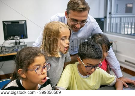Cute Multiethnic Children Learning With Help Of Happy Teacher. Lovely Kids Talking With Experienced