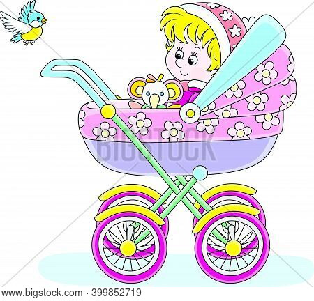 Happy Little Child Sitting In A Colorful Baby Carriage And Watching A Flying Small Bird On A Winter