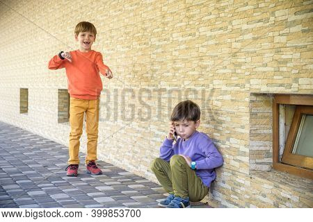 Portrait Of Little Boy Crying Hiding His Face With Cruel Kids Pointing At Him In Background, Bullyin
