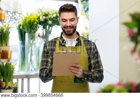 gardening, floristics and people concept - happy smiling male seller or florist in apron with clipboard over flower shop background