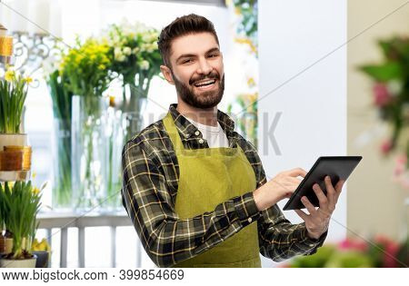 gardening, floristics and technology concept - happy smiling male seller or florist in apron with tablet pc computer over flower shop background