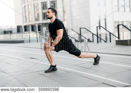Strong Man Doing Lunge Forward. Side View. Sport In Big City Concept. Fit Man Stretching Legs Before