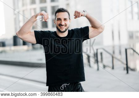 Cheerful Man Showing His Muscles. Hard Workout Concept. Fit Man Showing Biceps And Smiling. Gray Mor