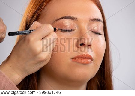 Closeup Photo Of Make Up For A Red-haired Girl, Closed Eyes And A Eyeliner Cosmetic Pencil. Beauty C