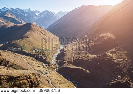 Long Narrow Canyon With River Stream Running Among Breathtaking Brown Steep Hills Against Mountains