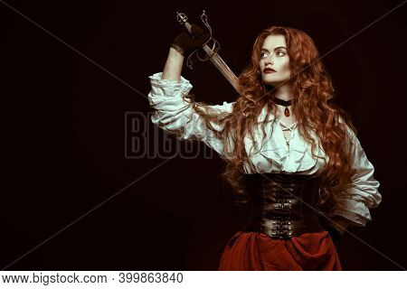 Portrait of a beautiful red-haired girl with a battle epee (rapier) on a black background. Historical reconstruction of the 16-17th centuries.