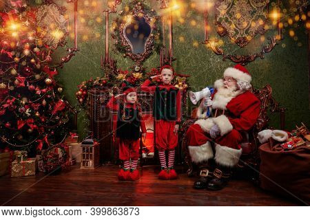 Santa Claus Support. Little elves helpers of Santa Claus prepare with him for Christmas at home. Merry Christmas and Happy New Year!