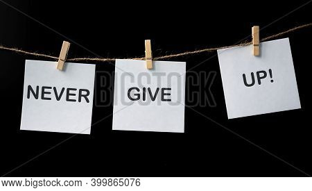 Motivational Phrase, Never Give Up, Wtitten On White Sticker On The Balck Background