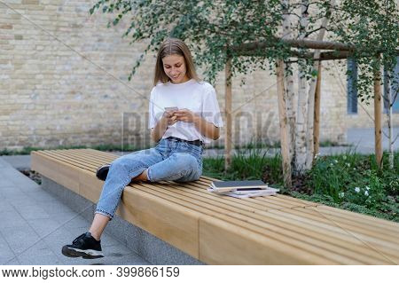 Full Length View Of Adult Highschool Student Girl Sitting Near Campus, Using Online App On Modern Sm
