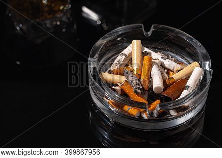 Ash Tray Full Of Cigarette Butts On Black Background