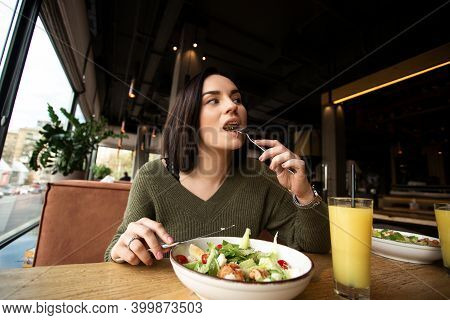 Young Woman Enjoys Tasty Meal. Attractive Woman With Brown Hair Slowly Eating Healthy Caesar Salad A