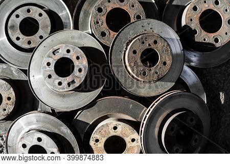 Old Used Car Brake Disc, A Lot Of Rusty Discs On A Gray Background