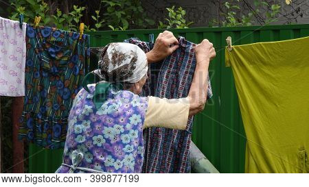 Great-grandmother With Traditional Head Scarf On Her Head Spreading And Hanging Colorful Washed Wet