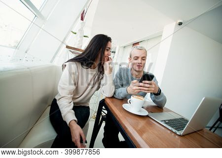 Young Couple Meets In Coffeehouse. Blonde Man Showing Something Fun In His Smartphone To Brunette At