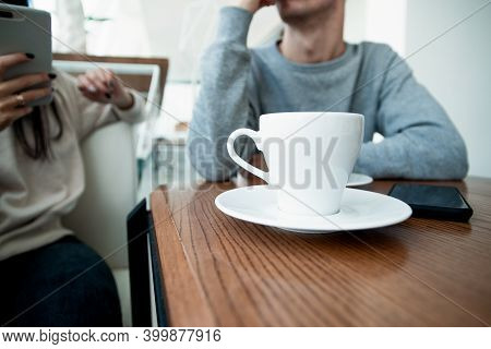 White Cup Of Coffe On Front. Blurred Couple On Background. Man And Woman On Romantic Date In Cafe. C