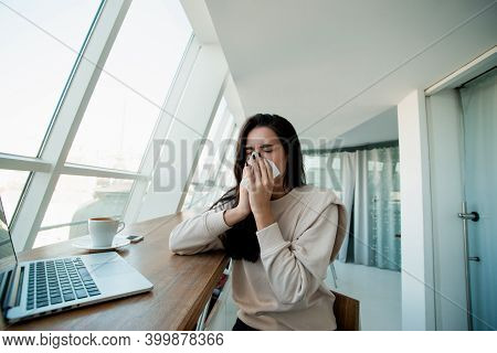 Young Woman Sneezes In Public Place. Freelancer Working On Her Modern Laptop At Coffeehouse Blows He