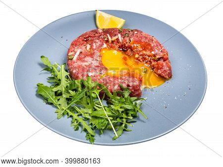 Served Steak Tartare (raw Minced Beef Meat And Chopped Onion With Raw Yolk Decorated By Fresh Arugul