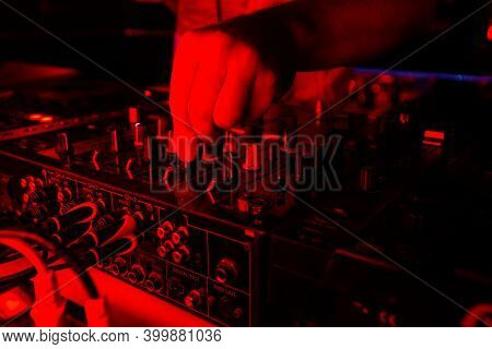 Dj Mixer In Bright Red Light. Cut Close Up Shot Of Male Hand Turning Tumblers On Disk Jockey Console