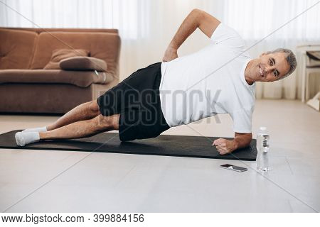 Cheerful Senior Man Doing Side Plank Exercise On Yoga Mat. How To Stay Healthy On Quarantine Concept