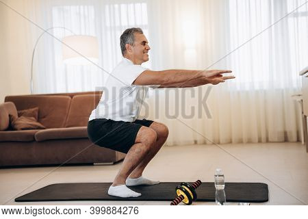 Workout Time Strong Senior Man Doing Squat Exercises At Home In His Light Living Room. Healthy Lifes