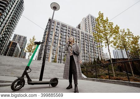 Woman Rented Scooter. Autumn In Big City. Attractive Woman In Casual Clothes Discusses Terms Of Rent